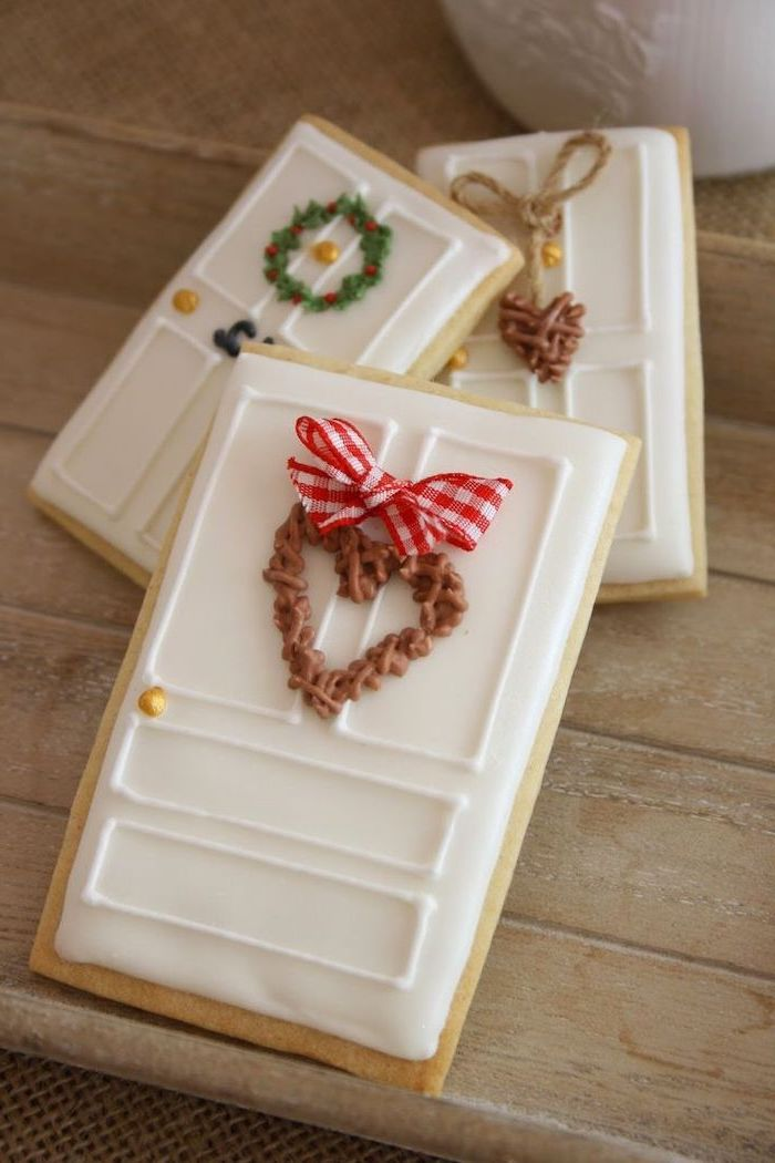 door shaped cookies, with wreath decorations on them, sugar cookie icing recipe, placed on wooden surface