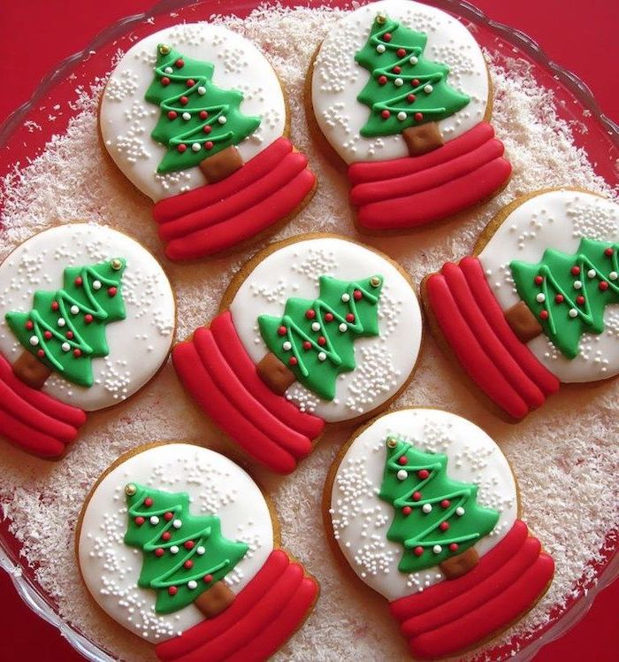 snow globe shaped cookies, cookie icing recipe, white red and green icing used for decoration, placed on faux snow in bowl