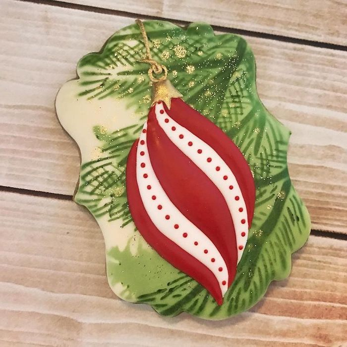 cookie painted with green and white icing, red ornament drawn on it, placed on wooden surface, cookie decorating icing