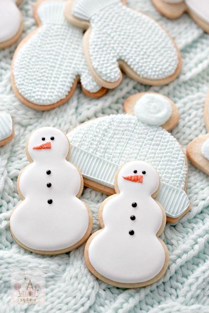 cookies in the shapes of snowmen mittens and beanie, cookie decorating icing, placed on white knitted cloth