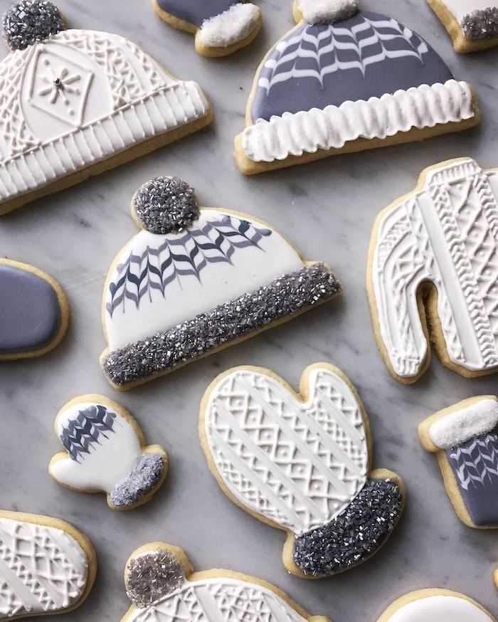 cookies in the shapes of beanies and mittens, cookie decorating icing, decorated with grey and white icing, placed on marble surface