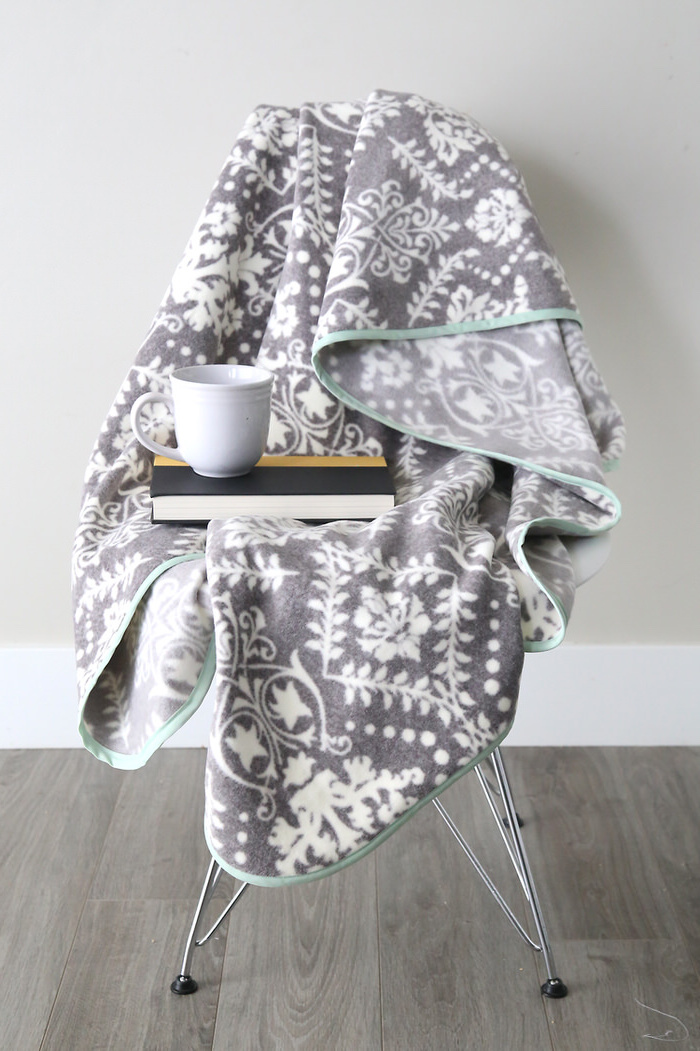 grey fleece blanket spread out on a chair, book and coffee mug on top of it, chair on wooden floor, christmas presents for moms