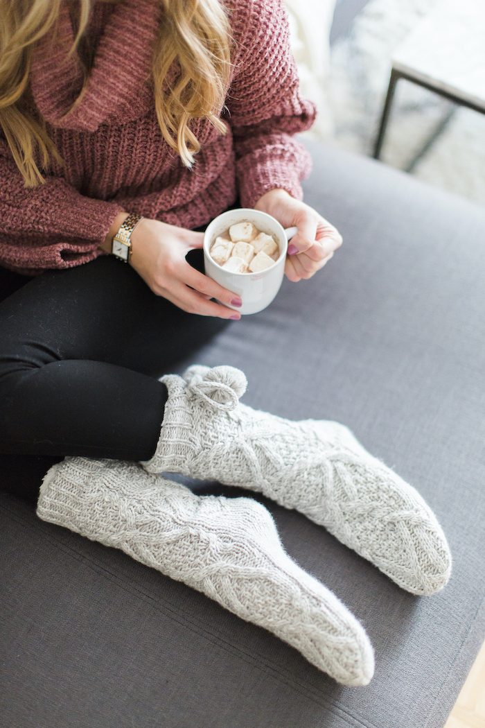 bonde woman wearing pink sweater and black tights, holding a cup with marshmallows, gifts for mom, grey knitted cozy socks
