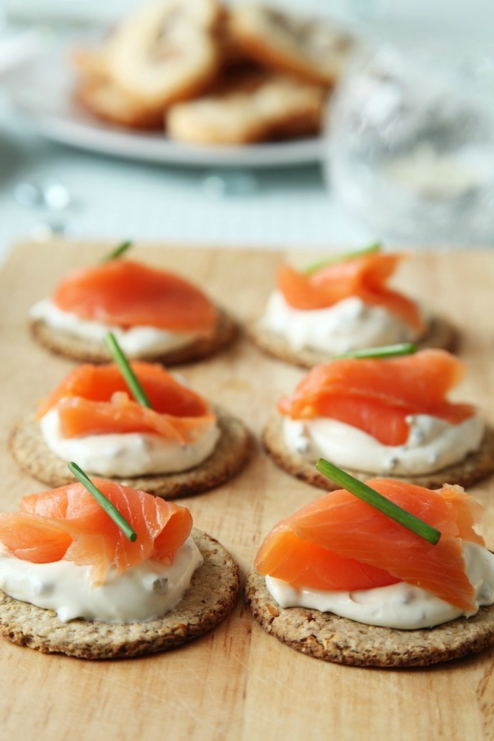 crackers with sour cream and salmon fillet, arranged on wooden board, easy christmas appetizers finger foods