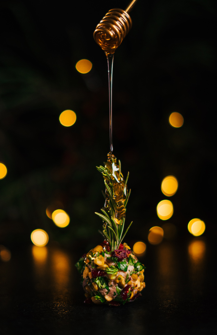 honey dripping over cream cheese ball, covered with different garnishes, cream cheese christmas appetizers