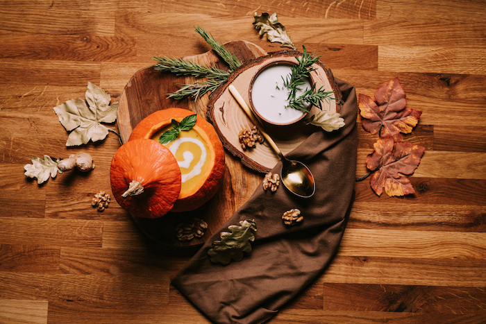 wooden table, fall arrangements on top, creamy chicken noodle soup, pumpkin soup, wooden board, brown table cloth, fall leaves