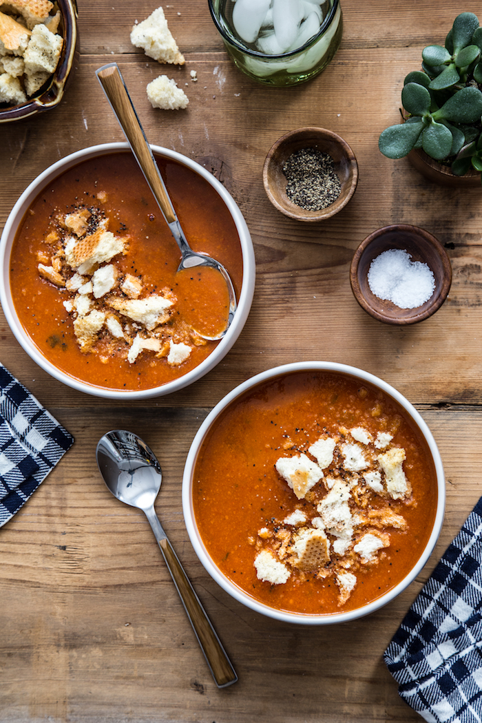 old fashioned potato soup, two bowls full of soup with croutons, small wooden bowls full of spices on wooden table