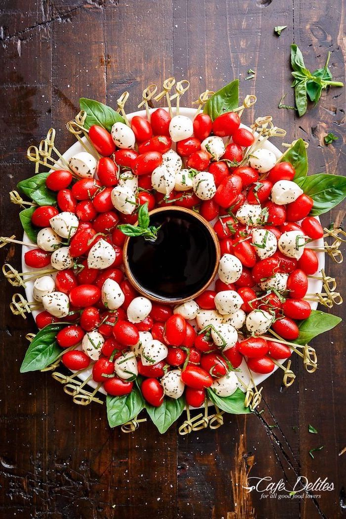 cherry tomatoes and baby mozzarella, basil leaves arranged as a wreath, easy christmas appetizers finger foods, bowl in the middle