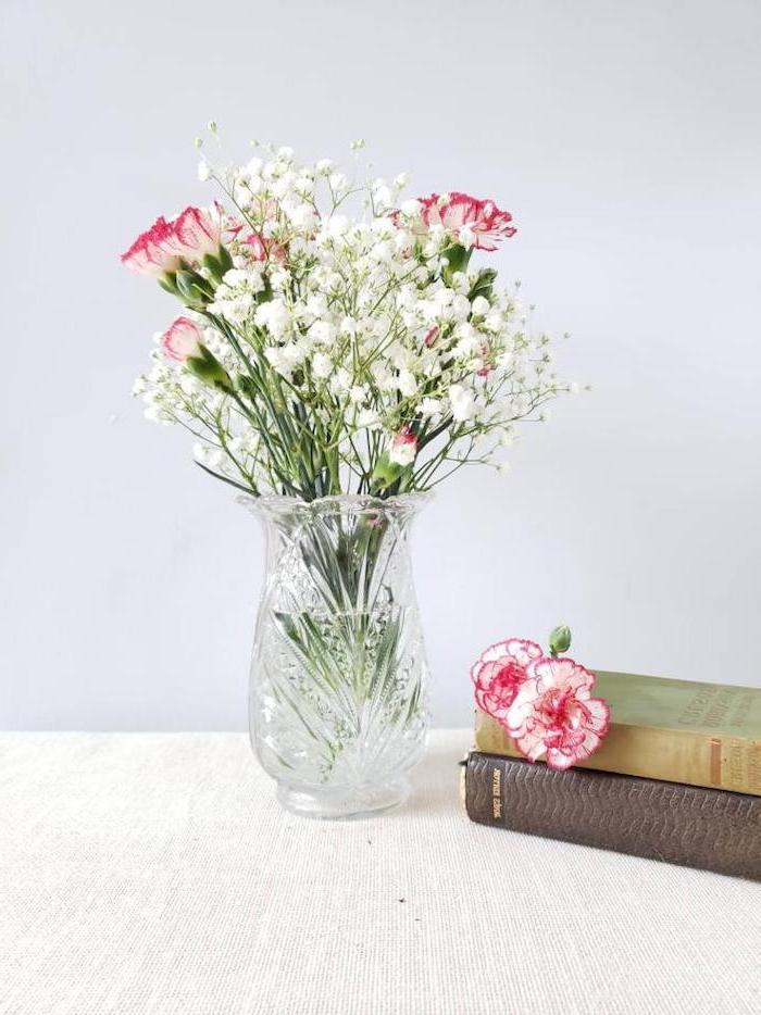 crystal vase with flowers inside, placed on wooden table, what to get your mom for christmas, two books on the side