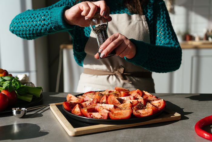 cut tomatoes arranged on black sheet pan, covered with black pepper, tomato soup, placed on wooden cutting board