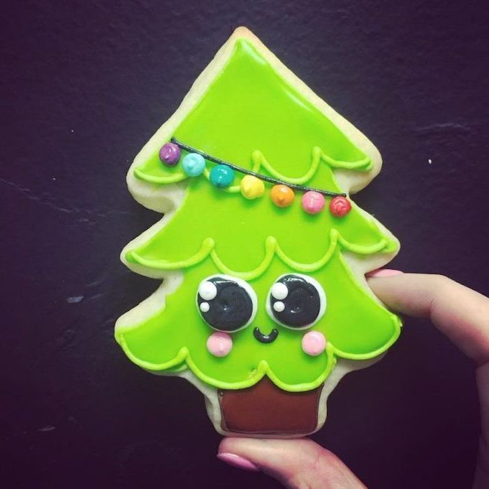 christmas tree shaped cookie, how to decorate sugar cookies, decorated with green and brown icing, placed on black surface
