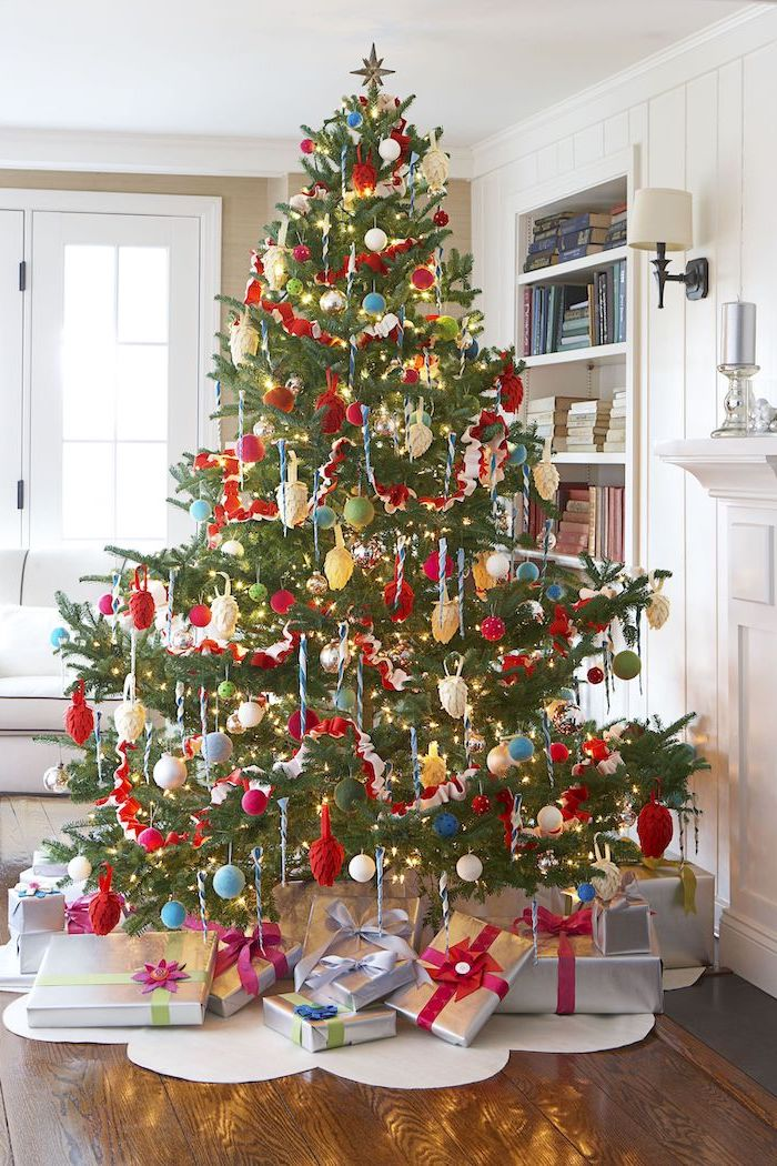 colorful christmas tree, decorated with red blue and green ornaments, wrapped presents underneath, place on white rug