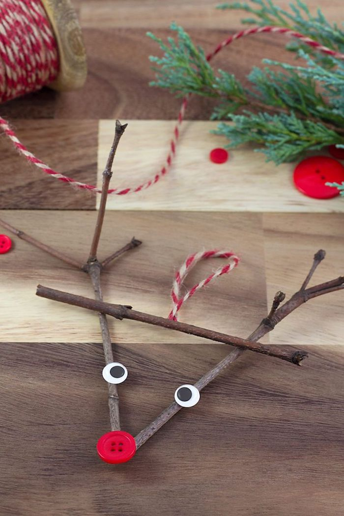 reindeer made of twigs, with googly eyes and red button for nose, preschool christmas crafts, placed on wooden surface