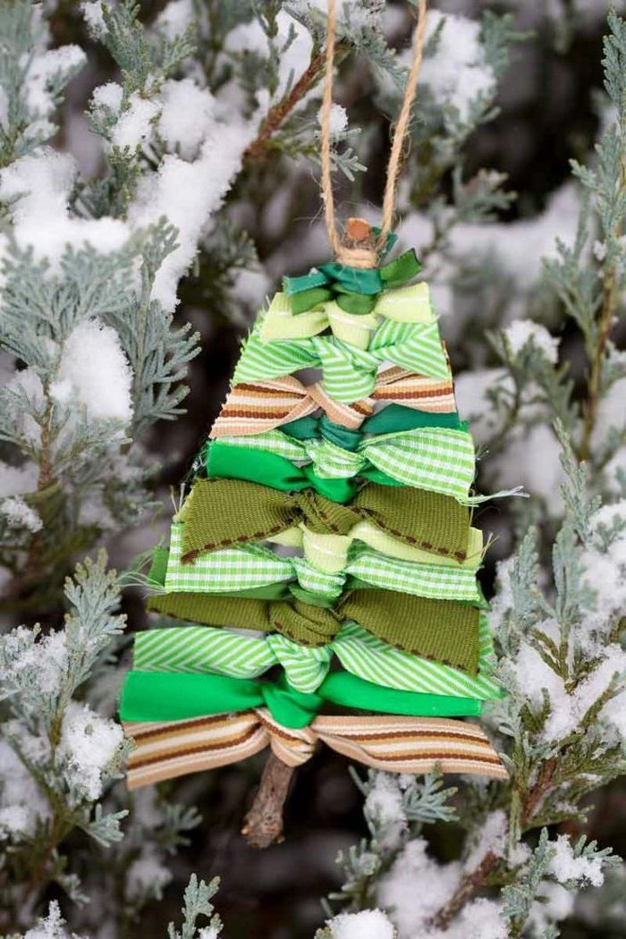 christmas arts and crafts, christmas tree ornament, made with a twig and ribbons with different patterns, hanging on a tree