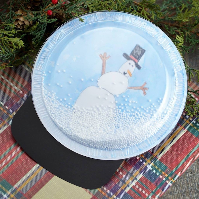 snow globe made of paper plate and plastic lid, faux snow inside, christmas ornament crafts, drawing of a snowman