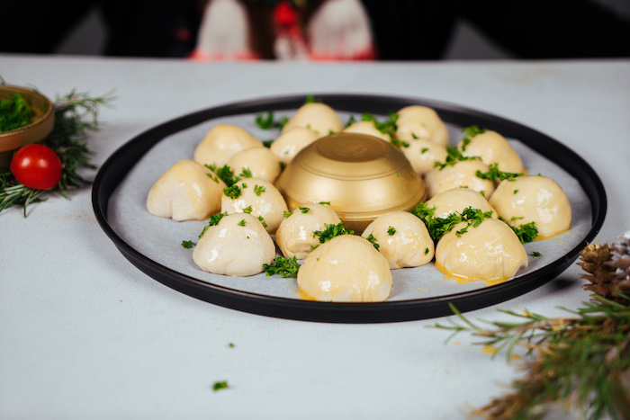 small dough balls, covered with chopped parsley, pull apart christmas bread, around a golden bowl, on baking sheet