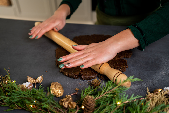 cookie dough being rolled out, spread on black surface, next to wreath with pinecones and lights, vegan gingerbread cookies