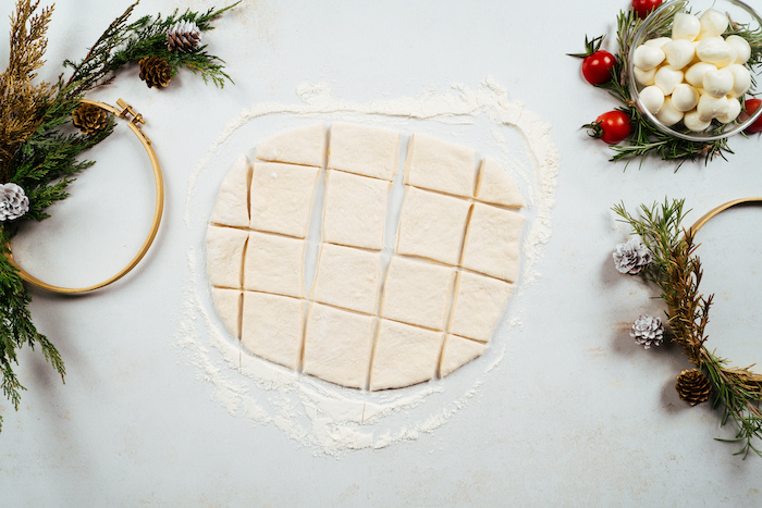rolled out dough, cut into squares, pull apart christmas bread, placed on lightly floured white surface