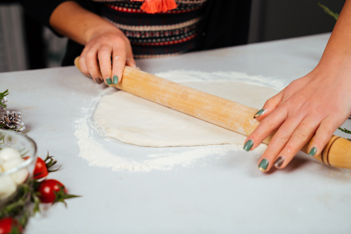 woman with green nail polish, rolling out dough on white surface, pull apart christmas bread, lightly floured surface