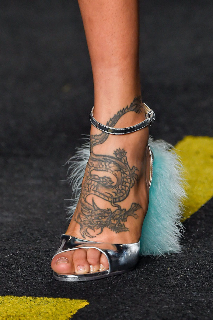 large dragon on the leg, woman wearing silver open toe heels with blue feathers, chinese dragon tattoo