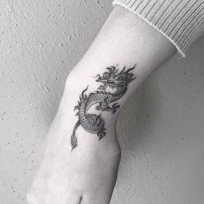 wrist tattoo, black and white photo, small dragon tattoos, white background
