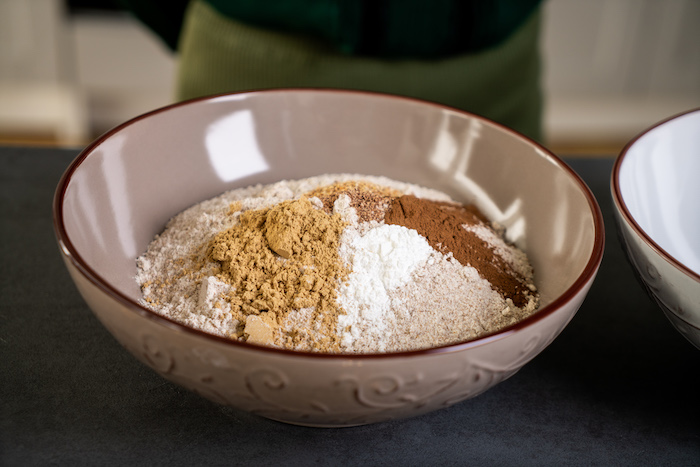 decorating gingerbread cookies, dry ingredients, mixed in a ceramic bowl, placed on black surface