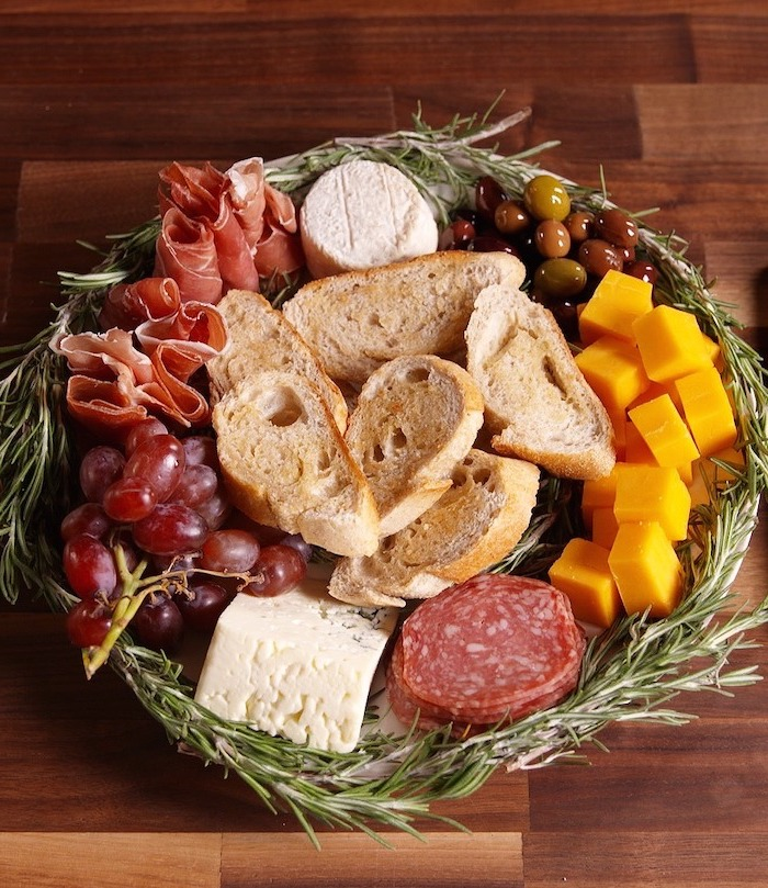 christmas appetizer recipes, wreath made of rosemary, different types of cheese and meat, olives and bread, placed on wooden surface