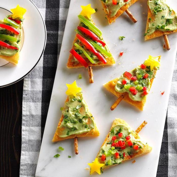 christmas tree shaped crackers, guacamole sauce and vegetables on top, christmas appetizer recipes, arranged on white board