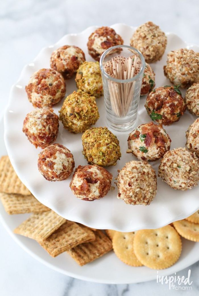 cheese truffles covered with different garnishes, finger foods for party, arranged around a small glass with toothpicks