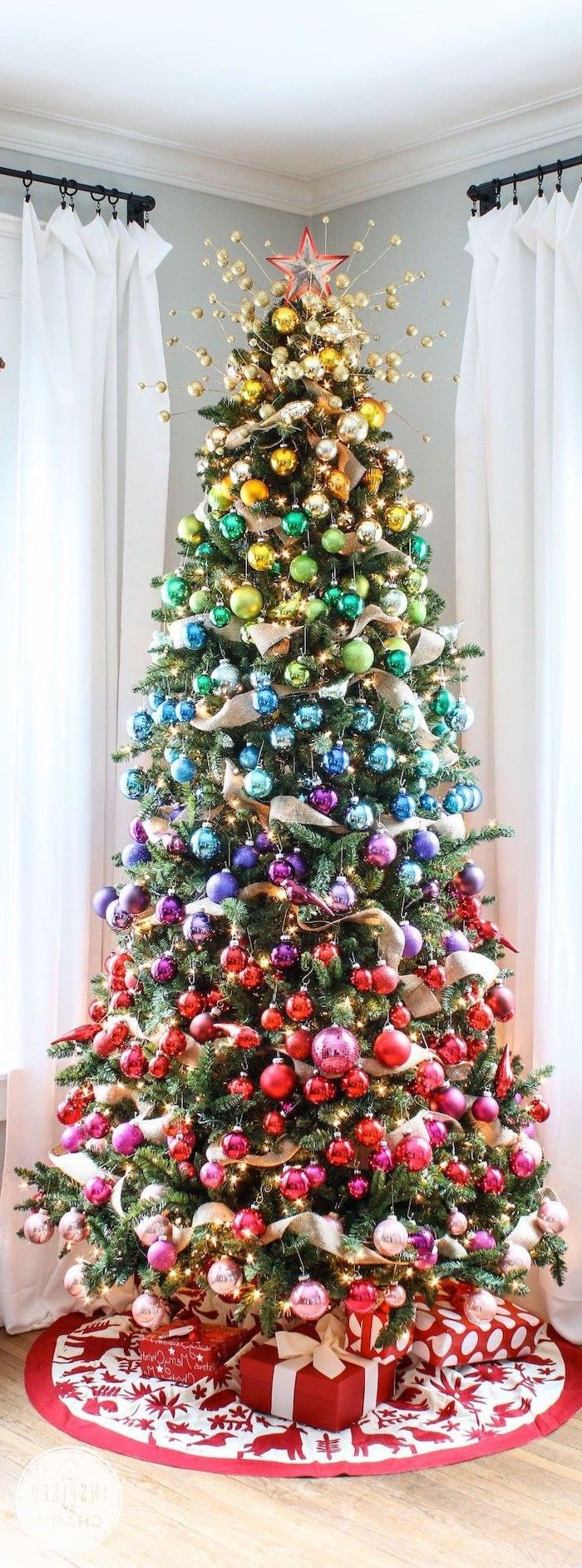 tall tree decorated in gradients colors of the rainbow, christmas tree ribbon, wrapped presents underneath