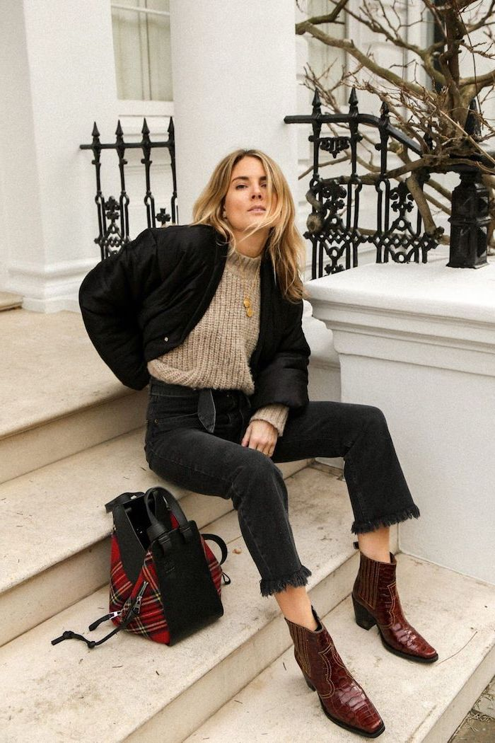woman sitting on stairs, wearing black jeans and brown sweater, new fashion trends, black jacket and red leather boots
