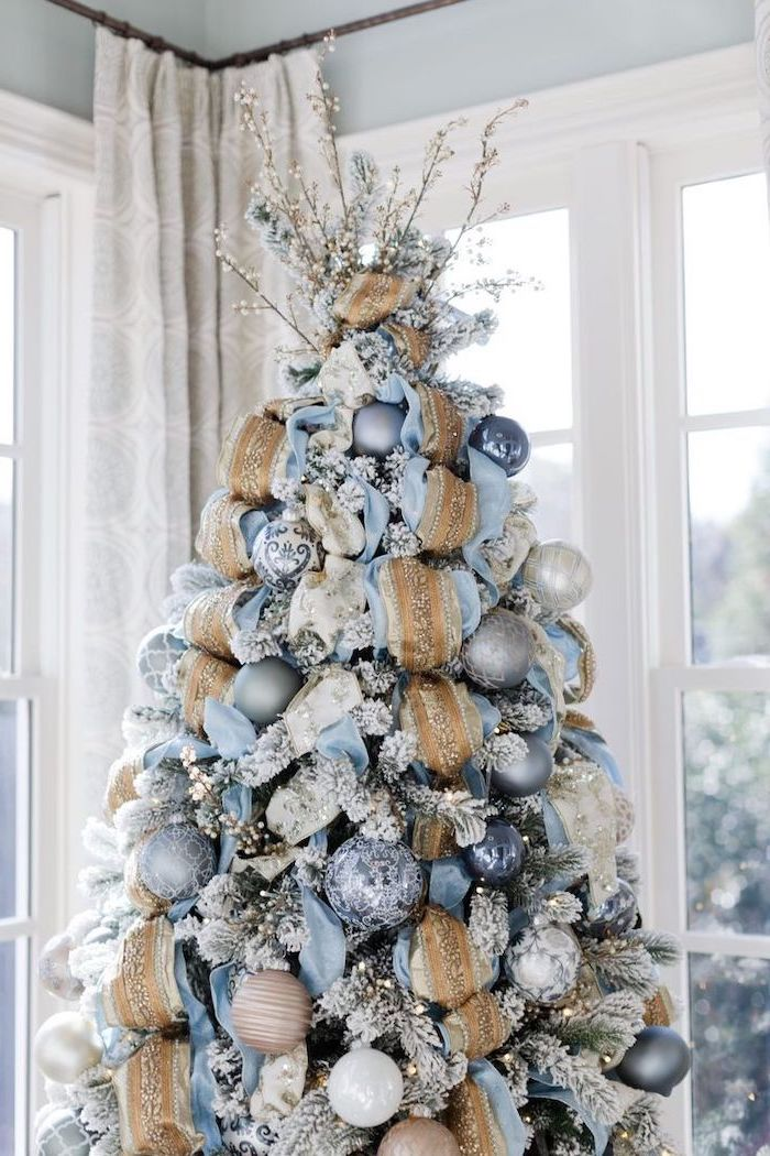 tree with faux snow, decorated with blue and gold ribbons, colorful christmas tree, blue and silver ornaments