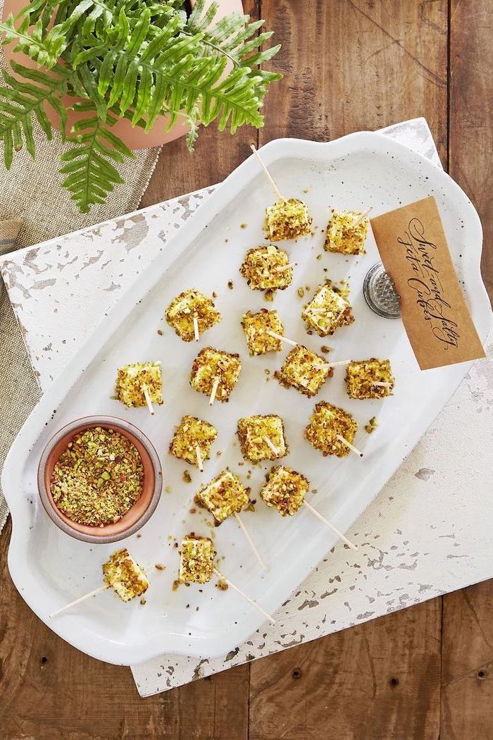 feta cheese cubes, covered with crushed nuts, christmas appetizer recipes, arranged on white plate, placed on wooden surface