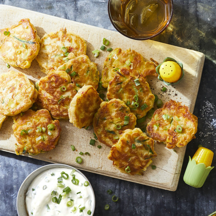 hash browns with chopped green onion on top, arranged on wooden board, christmas party finger foods, sour cream in a bowl
