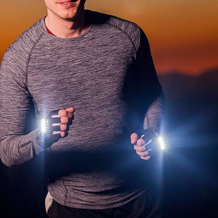 man wearing grey blouse, runner's led light gloves, what to get your boyfriend for christmas, sunset in the background
