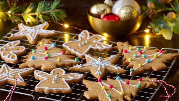 royal icing for decorating cookies, gingerbread cookies in different shapes, arranged on metal rail, snowflakes and angels