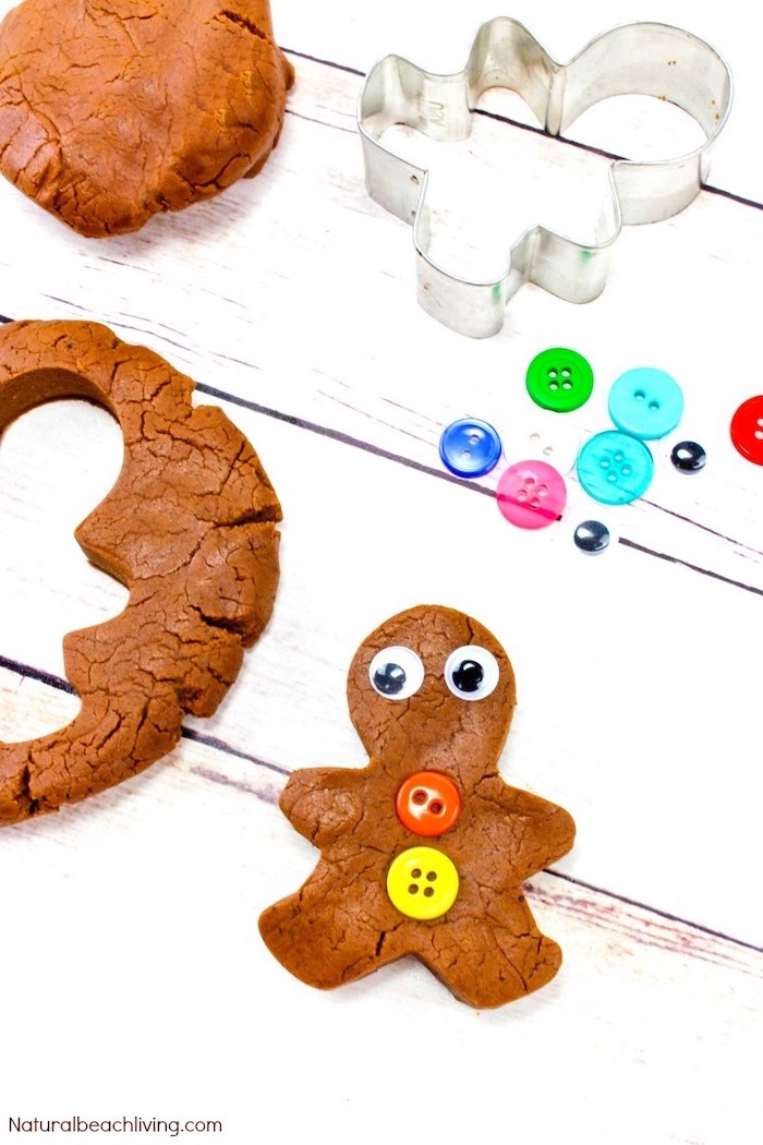 gingerbread man made out of play dough, christmas craft ideas for kids, colorful buttons placed on white wooden surface