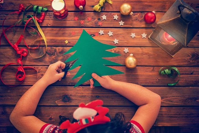girl cutting a christmas tree out of green paper, christmas craft ideas for kids, baubles placed on wooden surface