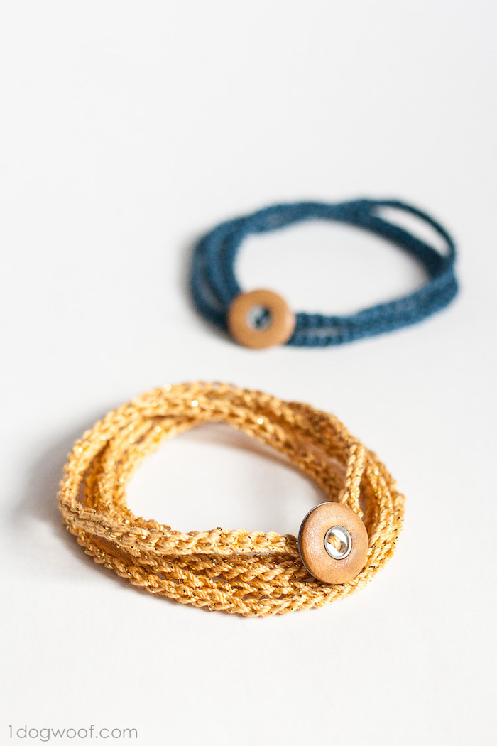 two crochet bracelets in gold and blue, gift ideas for men, with brown leather buttons, placed on white surface, step by step diy tutorial