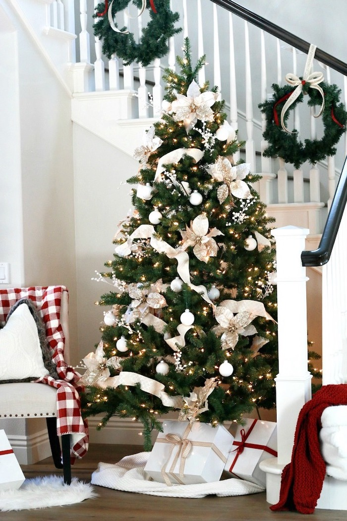 tree decorated with white flowers and ornaments, rose gold christmas tree, wrapped presents underneath, next to the staircase