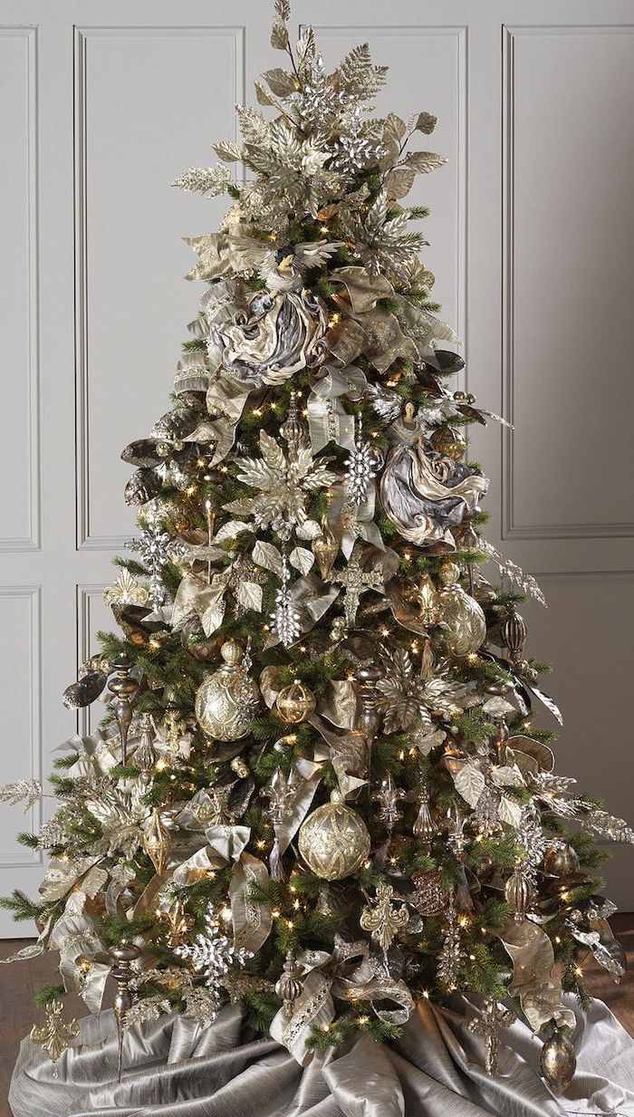 tree placed on grey silk rug, decorated with gold and silver ornaments, colorful christmas tree, faux flowers