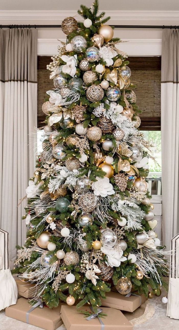 wrapped presents underneath a tree, decorated with gold and blue ornaments, rose gold christmas tree, white faux flowers