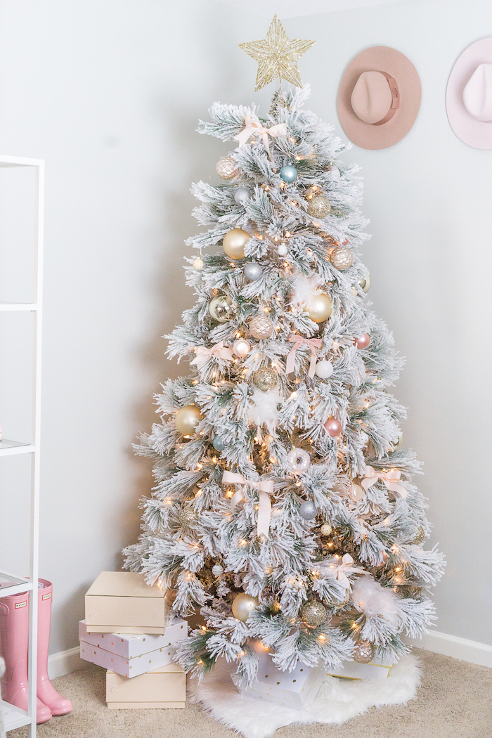 rose gold christmas tree, faux white tree, decorated with gold ornaments and pink bows, large gold star on top