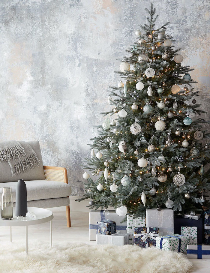 tree decorated with lights, white silver and gold ornaments, rose gold christmas tree, next to grey armchair, presents underneath