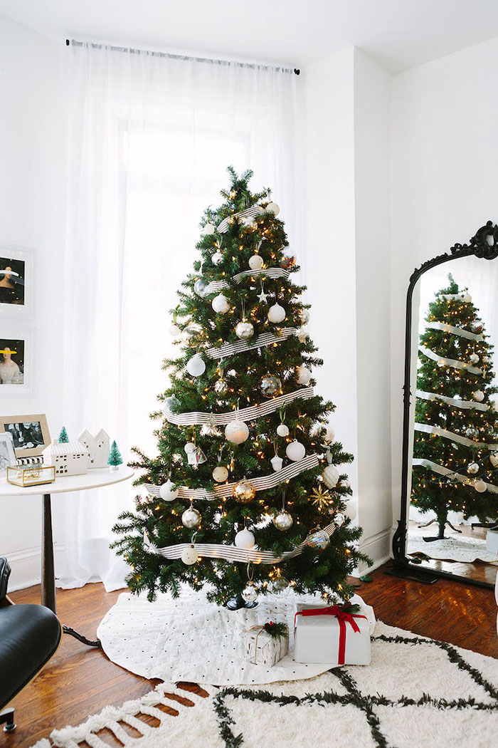tree placed on white rug, decorated with white ribbon and ornaments, rose gold christmas tree, on wooden floor