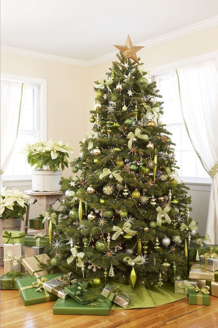 rustic christmas tree, gold star topper, tree decorated with green and silver ornaments, green bows, wrapped presents underneath