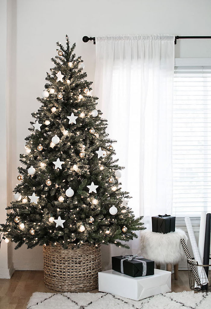 tree decorated with lights, white ornaments and stars, beautiful christmas trees, inside a basket on wooden floor