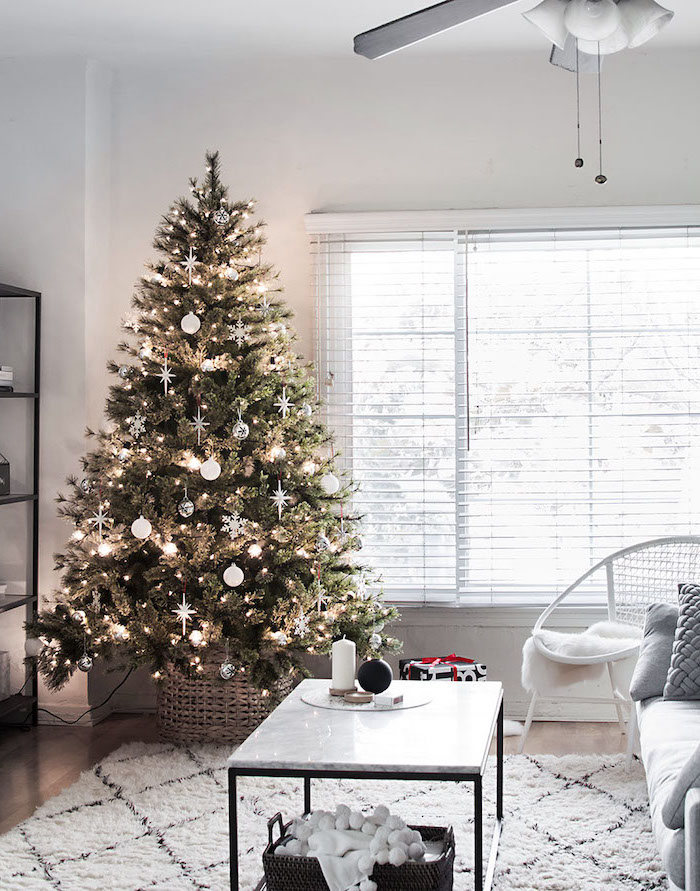 beautiful christmas trees, green tree with white ornaments and snowflakes, in wooden basket, with lots of lights