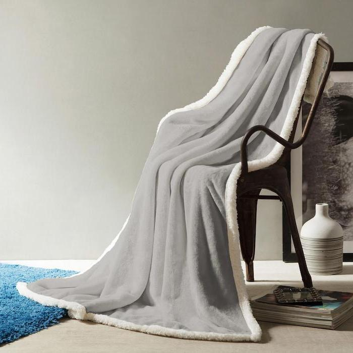 grey fleece blanket spread on a chair, falling to blue carpet, christmas gifts for mothers, art in the background