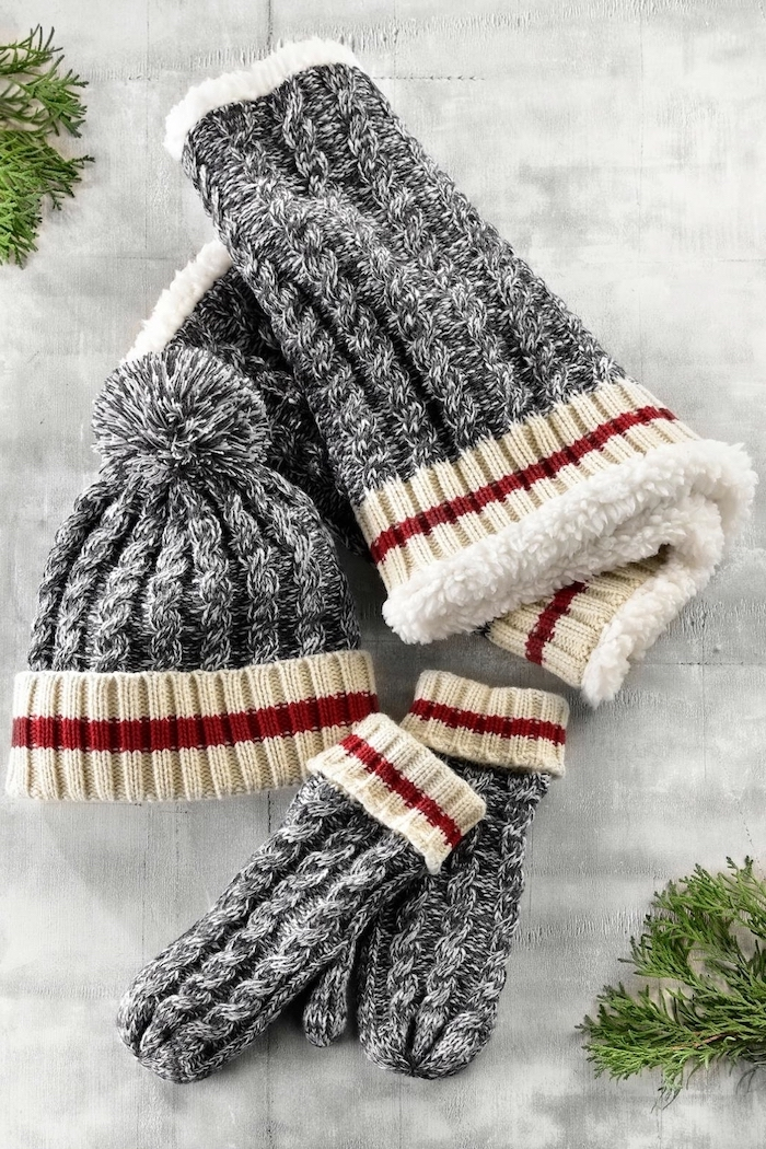 set of knitted mittens beanie and scarf, in grey beige and red, christmas gift ideas for mom, placed on white table